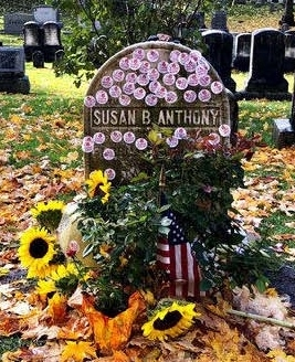 Susan B anthony grave stone decorated with I Voted stickers